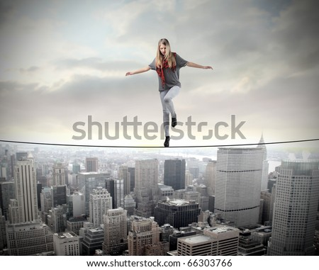 Beautiful woman standing on a rope over a cityscape - stock photo