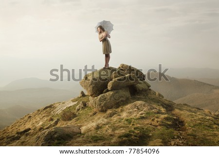 Beautiful woman standing on a stone and holding an umbrella