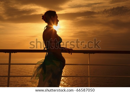 beautiful woman standing on deck of cruise ship and looking away. sunset. - stock photo