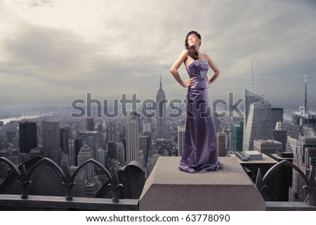 Beautiful woman standing on the rooftop of a skyscraper - stock photo