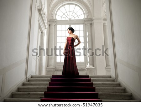 Beautiful woman standing on the top of a stairway - stock photo