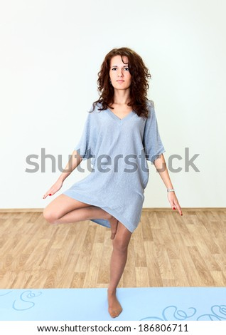 Beautiful woman standing one leg, doing fitness at domestic room