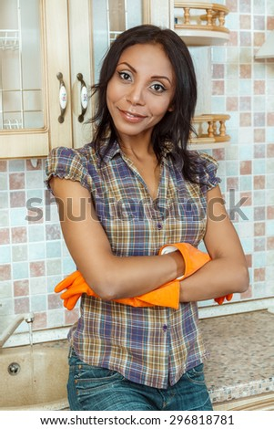 Beautiful woman standing with arms crossed in kitchen.