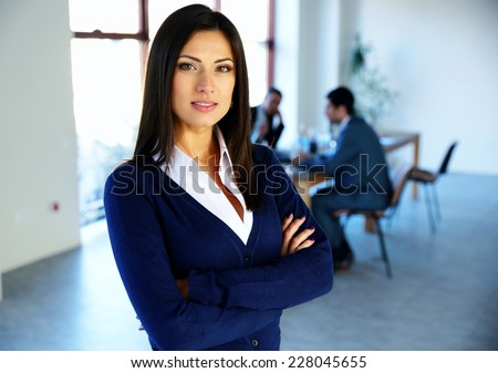 Beautiful woman standing with arms folded with colleagues on background - stock photo