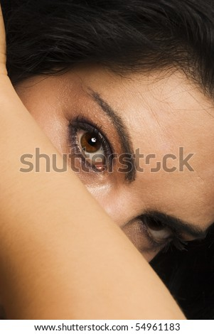 Beautiful woman  standing with head inclined,hidden her face with hand  and looking  with big eyes to side,at camera