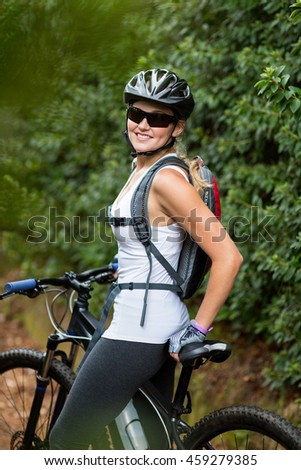 Beautiful woman standing with mountain bike on countryside