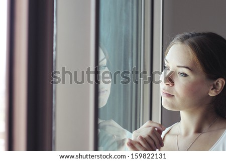 beautiful woman stands in front of the window - stock photo