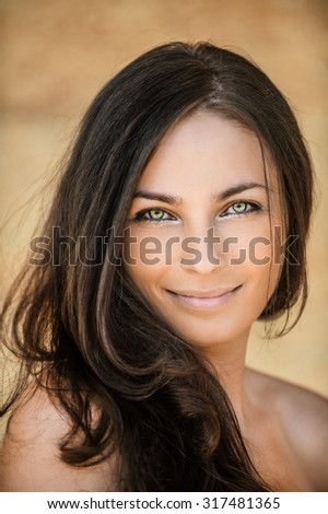 beautiful woman stands sideways dark hair bare shoulder smiling - stock photo