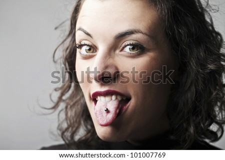 Beautiful woman sticking out her tongue and showing her piercing - stock photo