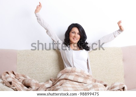 Beautiful woman stretching her body after she wake up on the sofa in home - stock photo