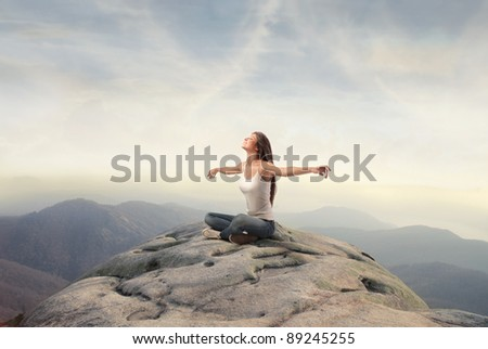 Beautiful woman stretching out her arms while sitting on a peak over the mountains - stock photo