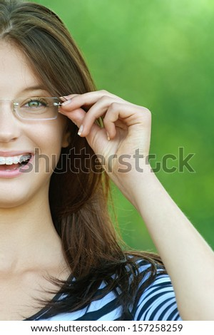 beautiful woman striped dress park raised glasses forehead - stock photo