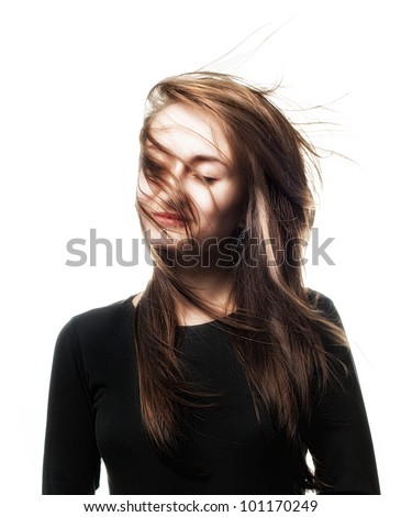 Beautiful woman studio portrait with wind on hair on face isolated on white - stock photo