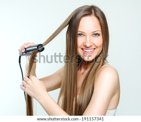 beautiful woman styling her long natural hair. straight hair. - stock photo