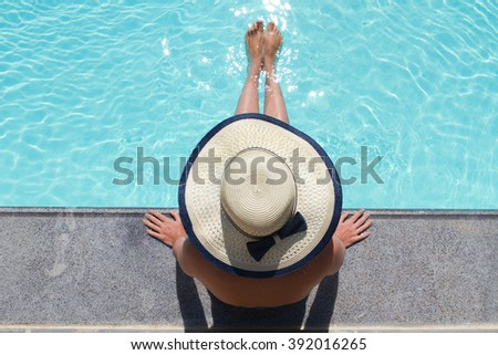 Beautiful woman sunbathing by the pool top view. Summer background.