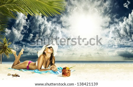 Beautiful woman sunbathing on a beach - stock photo