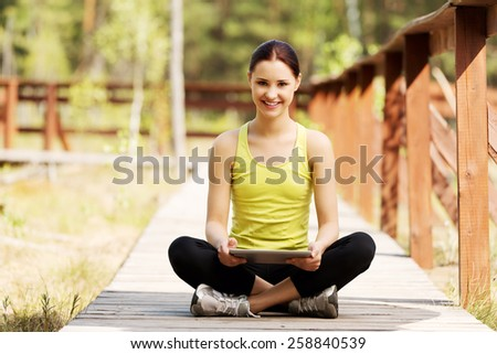 Beautiful woman surfing on tablet after running - stock photo
