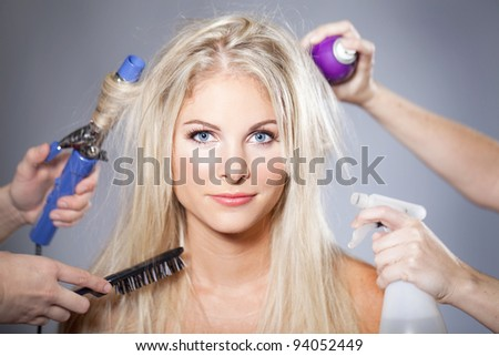 Beautiful woman surrounded by hair care tools - stock photo