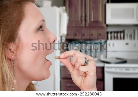 Beautiful woman taking a pill or medicine or medication - stock photo