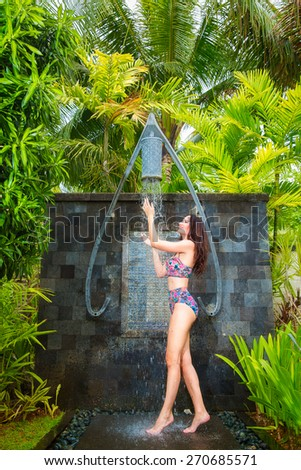 Beautiful woman taking a relaxing shower at the hotel on a tropical island. Summer vacation concept. - stock photo