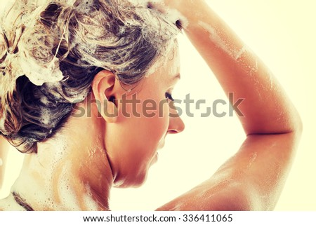 Beautiful woman taking a shower and shampooing her hair. - stock photo