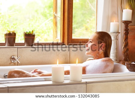 Beautiful woman taking bath at home, cute female lying down in bathtub, warm candle light, romantic atmosphere, pampering and hygiene, spa resort in hotel, zen balance concept - stock photo
