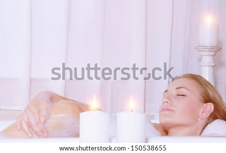 Beautiful woman taking bath with closed eyes, bathing at luxury spa resort, beauty treatment, health care, pampering, relaxation at home, wellness concept - stock photo