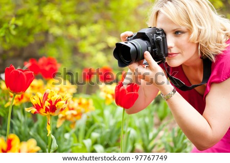 Beautiful woman taking photographs of tulips in a spring garden - stock photo