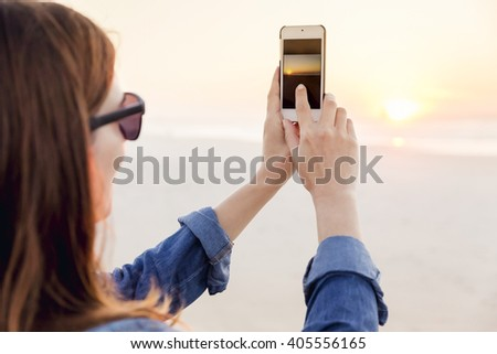 Beautiful woman taking pictures with a cellphone - stock photo