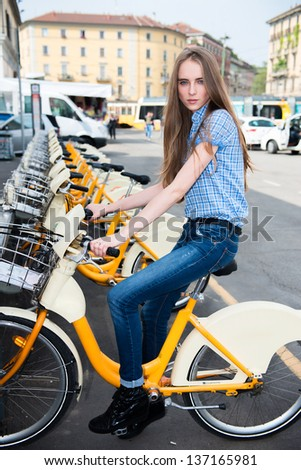 Beautiful woman taking rent bicycle in the city