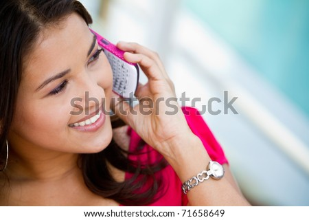Beautiful woman talking on her cell phone - stock photo