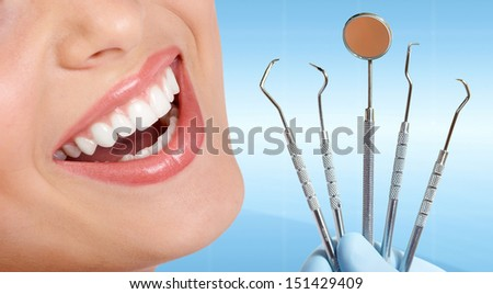 Beautiful woman Teeth with dental tools. - stock photo