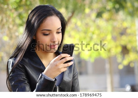 Beautiful woman texting on a smart phone in a park with a green background - stock photo