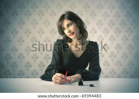 Beautiful woman thinking while writing - stock photo
