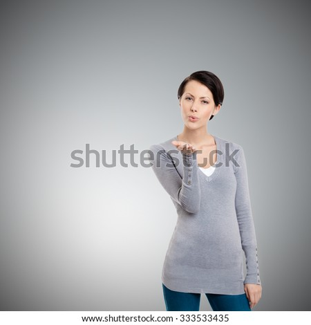 Beautiful woman throws a kiss, isolated on grey - stock photo