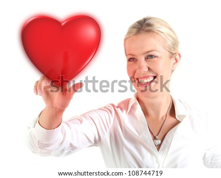 Beautiful woman touching a heart with finger - stock photo