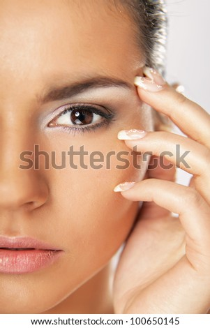 beautiful woman touching face and looking at camera winks