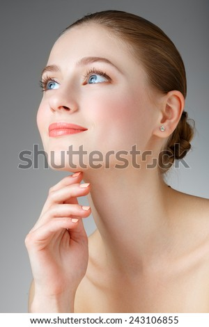 Beautiful Woman Touching her neck. Perfect Fresh Skin. Pure Beauty Model. Youth and Skin Care Concept. Smiling girl with blue eyes. Portrait of a beautiful woman with a smile. - stock photo