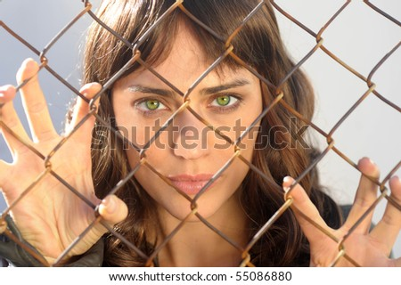 Beautiful woman trapped behind a fence - stock photo
