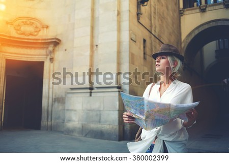 Beautiful woman traveler holding location map in hands while looking for some direction in urban scene in sunny summer day, young female student checking out the sights on atlas during trip overseas  - stock photo