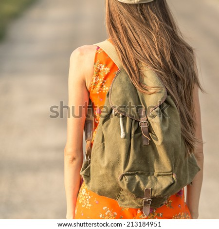 Beautiful woman traveling with vintage backpack. focus on backpack - stock photo