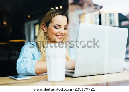 Beautiful woman typing on laptop at cafe - stock photo