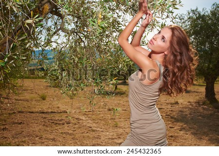 Beautiful woman under an olive tree - stock photo