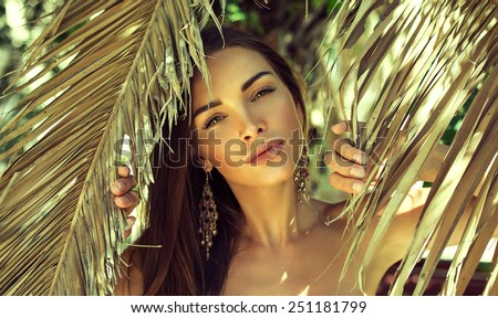 Beautiful woman under palm tree - stock photo