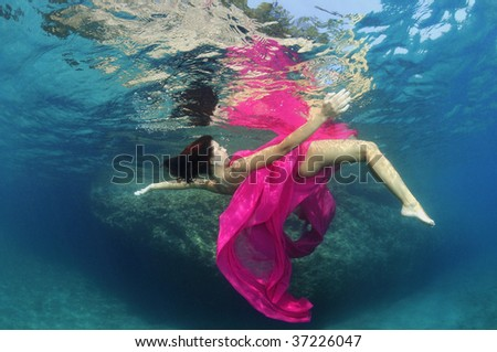 Beautiful woman underwater wrapped in pink fabric - stock photo