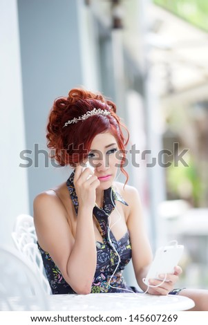 Beautiful woman upset and crying,  She using smartphone listen melancholic music or get unhappy phone call while sitting at outdoor cafe, model is Thai Ethnicity. - stock photo