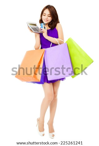 beautiful woman using a calculator and holding bags. saving money concept. - stock photo