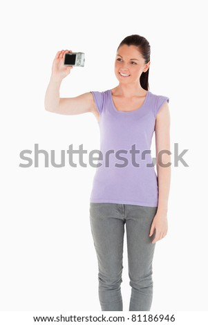 Beautiful woman using a camera while standing against a white background