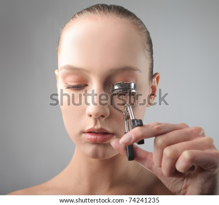 Beautiful woman using an eyelash curler - stock photo