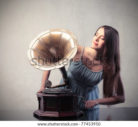Beautiful woman using an old gramophone - stock photo